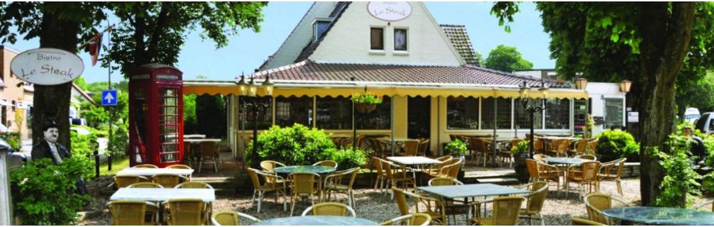 Het restaurant en het terras. Je kan de gezellige en rustieke sfeer al zien aan het gebouw.